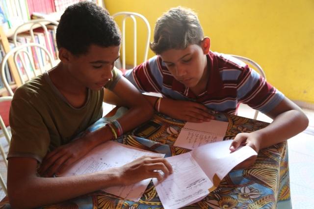 Rafael Varão (coordenador da biblioteca Folhas da Vida) e Matheus Sá (Latinhas de Quintal) estudem o primeiro boneco do novo jornal comunitário Nem Um Pingo que vão  lançar na semana depois do Dia das Mães.