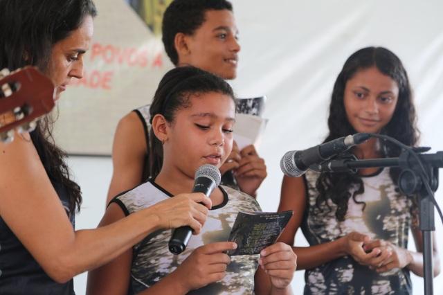 Viviane do projeto Biblioteca Folhas da Vida le o poema Vento Norte na Feira de Sementes Tradicionais.