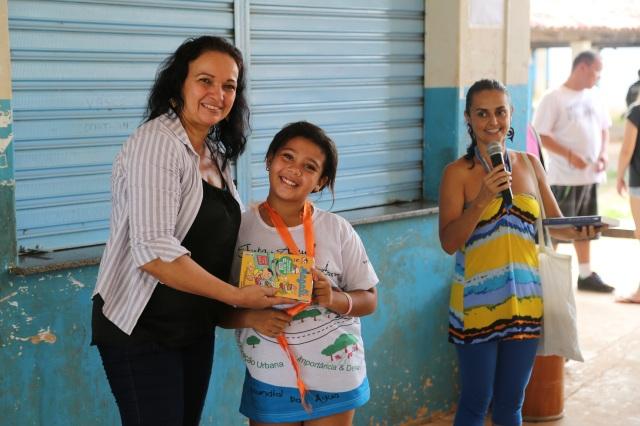 Viviane Suares do micro-projeto Biblioteca Folhas da Vida entrega livros a diretora Sheila Luiza no ato de celebrar a escola Jonathan Pontes Athias como parceira do Rios de Encontro.