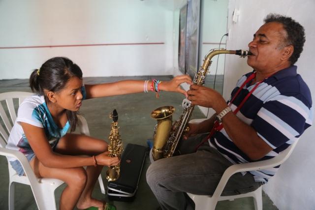 Artista e arte educadora Evany Valente (15 anos) ensina mestre Zequinha numa aula de sax. Ambos vão oferecer cursos no Festival de Verão.