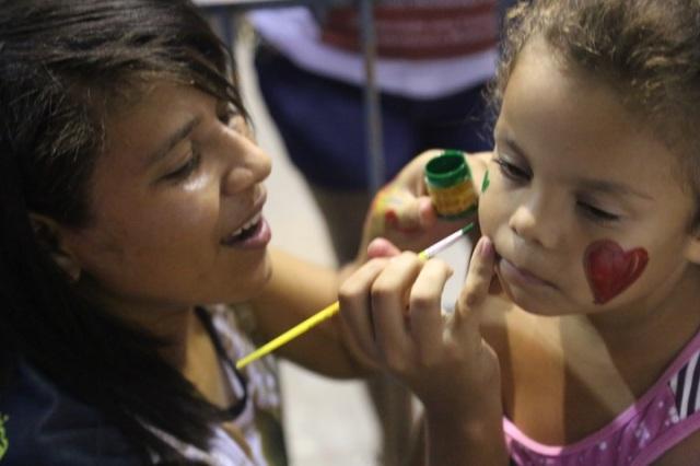 Carol, uma dos coordenadores de Folhas da Vida, ministra a oficina de pintura de rosto durante a primeira noite do festival, na Mendonça Cultural.