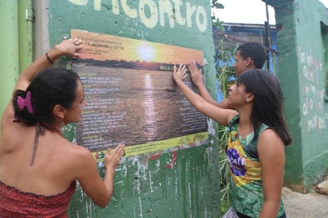 Manoela, Carol e Pablo colam um minidoor fora do barracão para completar a divulgação do festival dentro da comunidade Cabelo Seco.