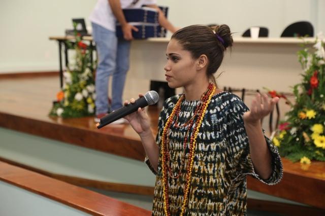 Camylla explica o processo de pesquisa pós apresentação como parte da apresentação sobre os princípios pedagógicos de nossa Universidade Comunitária do Rios.